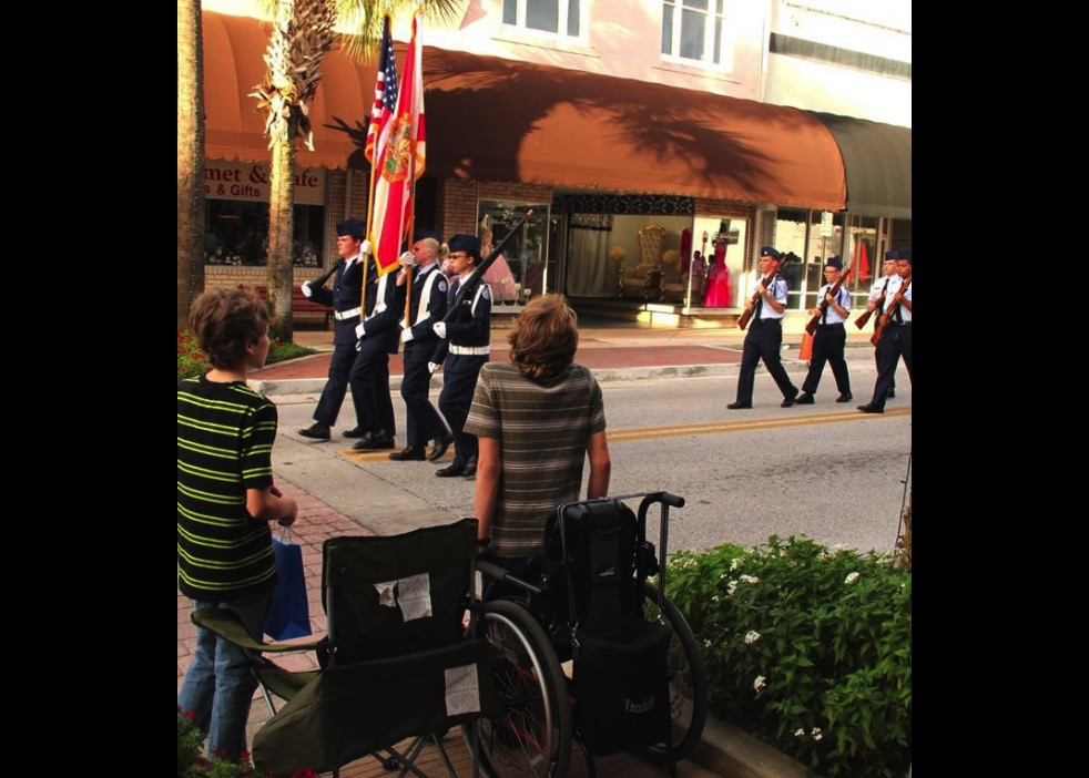 wheelchair boy stands for flag